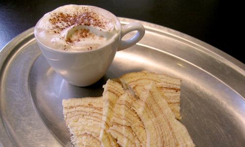 Kaffee und Baumkuchen auf silbernem Tablett